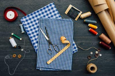 Stoffreste wiederverwenden, Stoffe mit Schere, Maßband und verschiedene Fadenspulen