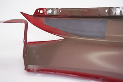 Close up of pre-formed structural patch installed on a red painted car body used to fill open areas and seal open gaps, on a white background