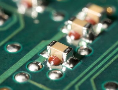 Photo of small surface mount  electrical components on a green printed circuit board using henkel surface mount adhesive solutions