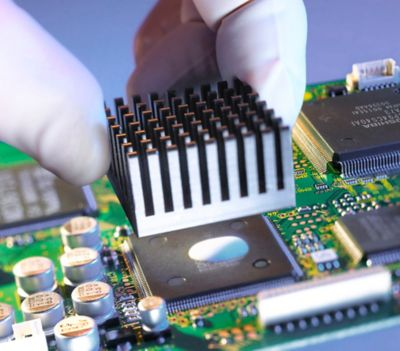 Photo of white gloved technician attaching heatsink to top integrated circuit with thermally conductive adhesive