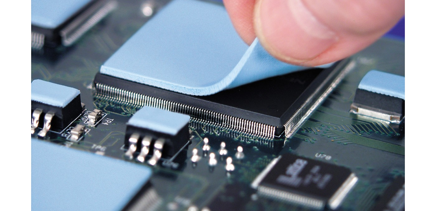 Photo of blue  thermal gap pad being placed on top of an electronic component on a pcb with other blue thermal gap pads on other components elsewhere on the pcb assembly