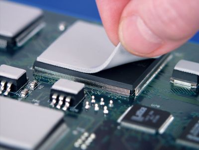 Photo of light grey  thermal gap pad being placed on top of an electronic component on a pcb with other light grey thermal gap pads on other components elsewhere on the pcb assembly