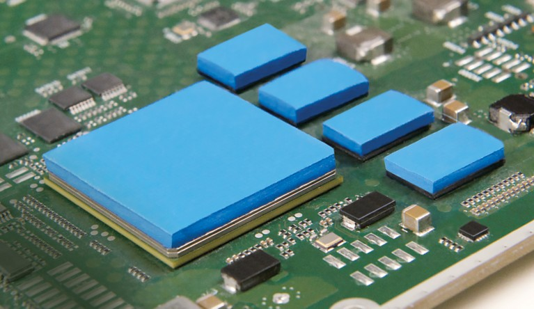 Photo of blue thermal interface material on top of components on a green pcb