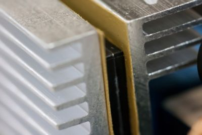 Close up photo of electronic component sandwiched between two metal heat dissipation fins and bonded to the metal fins with a thermal interface material