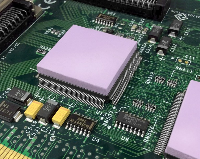Photo of light purple thermal interface material on top of electronic components on a green pcb