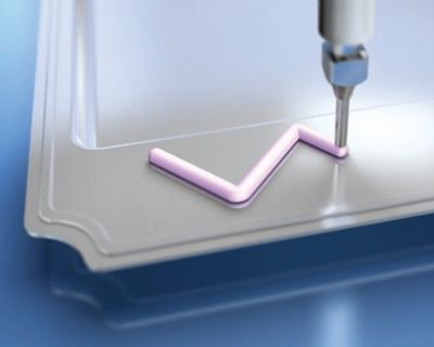 Photo of pink bergquist thermally conductive liquid gap filler being dispensed on metal