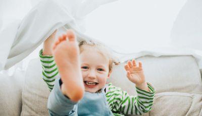 Nasmijano dijete rukom i nogom podiže bijelu tkaninu