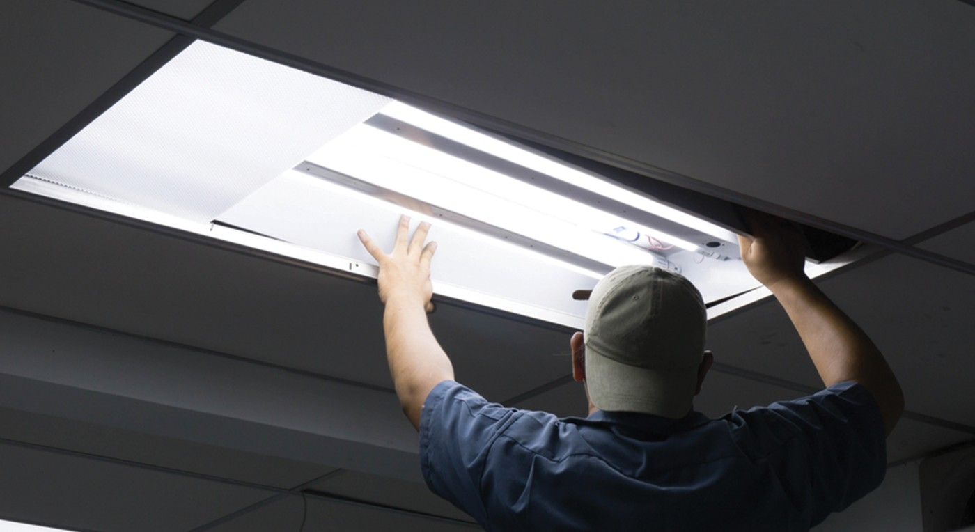 Photo of maintenance worker in blue shirt and green baseball cap installing fluorescent or led tube lights in an overhead light fixture shutterstock ID 728509933