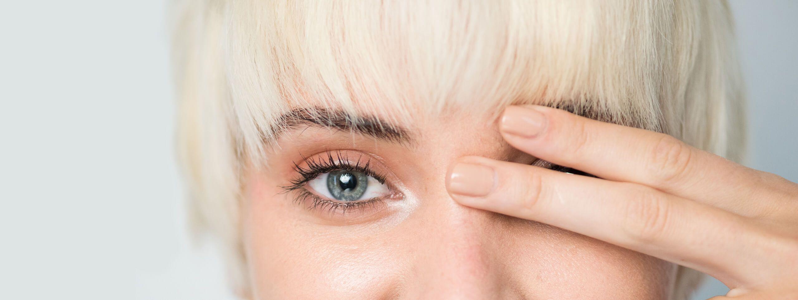 Twarz kobiety z krótkimi blond włosami częściowo zasłonięta palcami