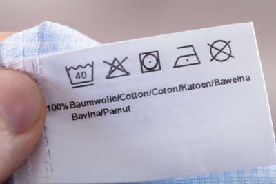 Pflegeetikett mit Waschsymbolen für ein Kleidungsstück aus Baumwolle