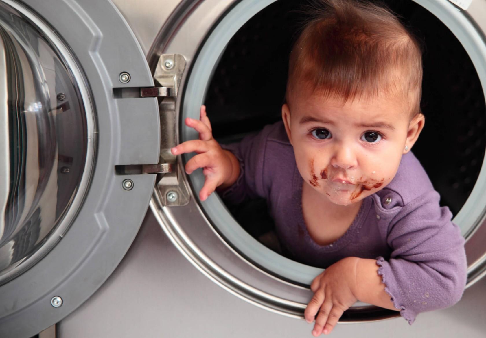 Kleinkind mit schokoladenverschmiertem Mund guckt aus einer Waschtrommel heraus