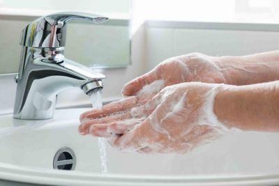 Händewaschen, eingeseifte Hände unter einem laufenden Wasserhahn.
