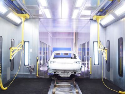 White car body undergoes Henkel's Two-Step Surface Treatment process during the manufacturing