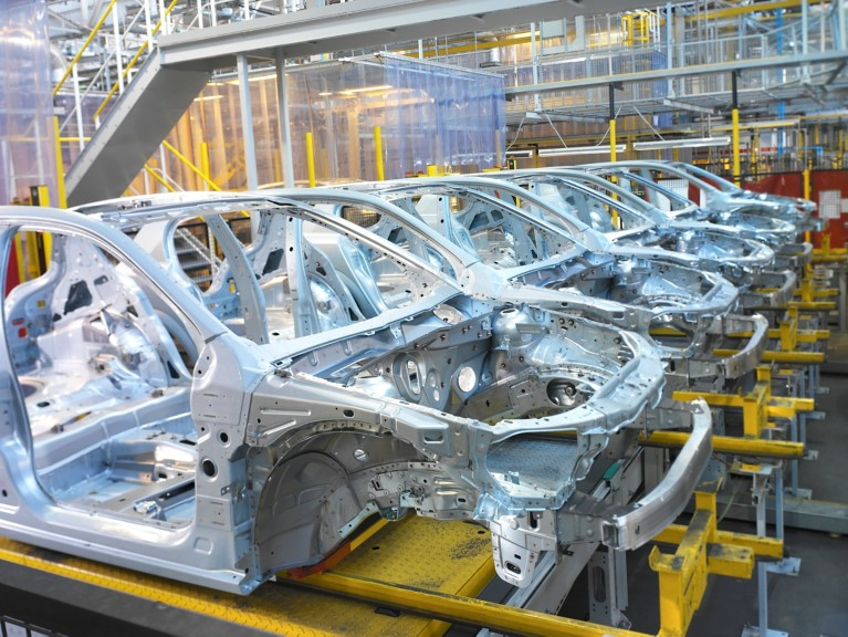 Row of white car frames inside automotive manufacturing site