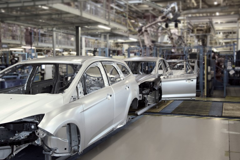 White vehicle frames in a factory automotive manufacturing site