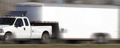 Work truck with trailer attached driving on a highway