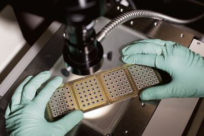 Scientist holds strip of die attach paste