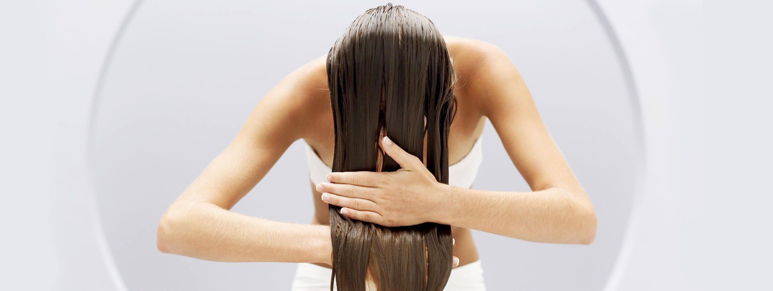 Woman applies hair treatment to long hair