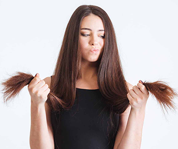 Woman examines dry split ends of hair