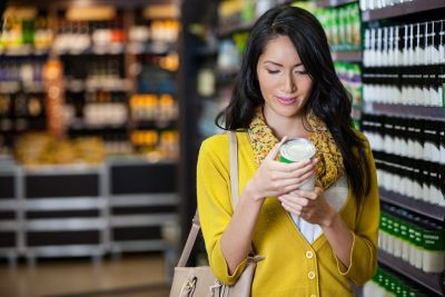 Woman in a grocery store holding a food can