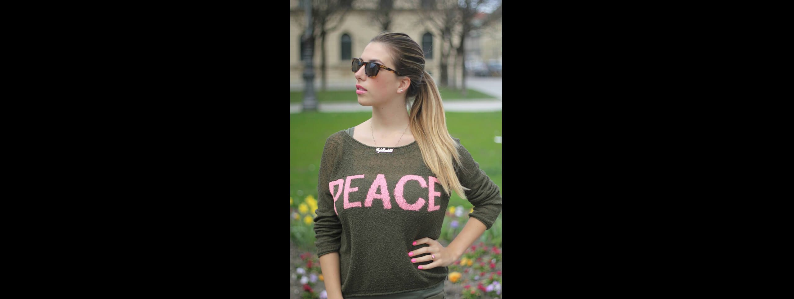 Woman wearing a peace shirt with golden brown hairstyle