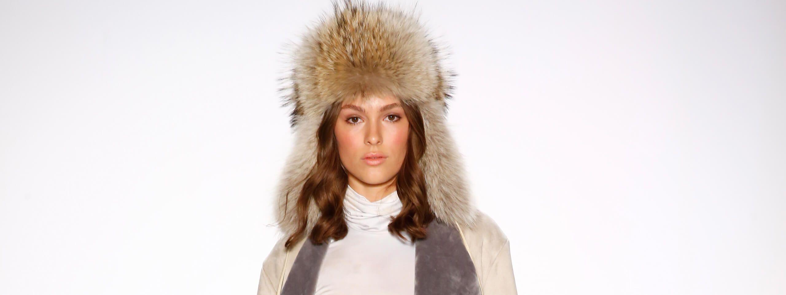 Woman wears brown wavy hairstyle under winter hat