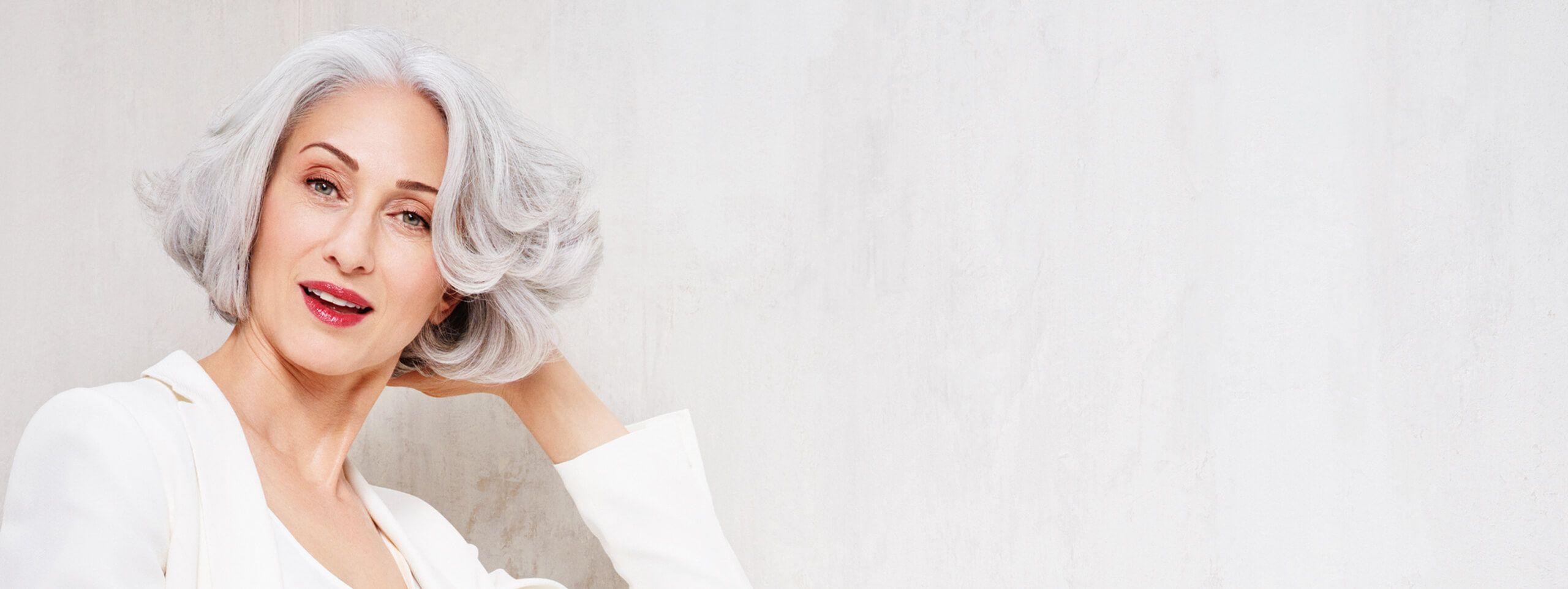 Woman wears light gray hair in a wavy bob hairstyle