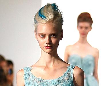 Woman wears short blonde updo hairstyle with blue streaks