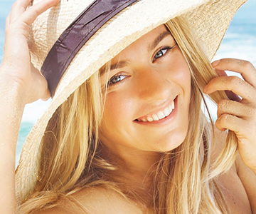 Woman with a blonde hairstyle at the beach wearing a hat