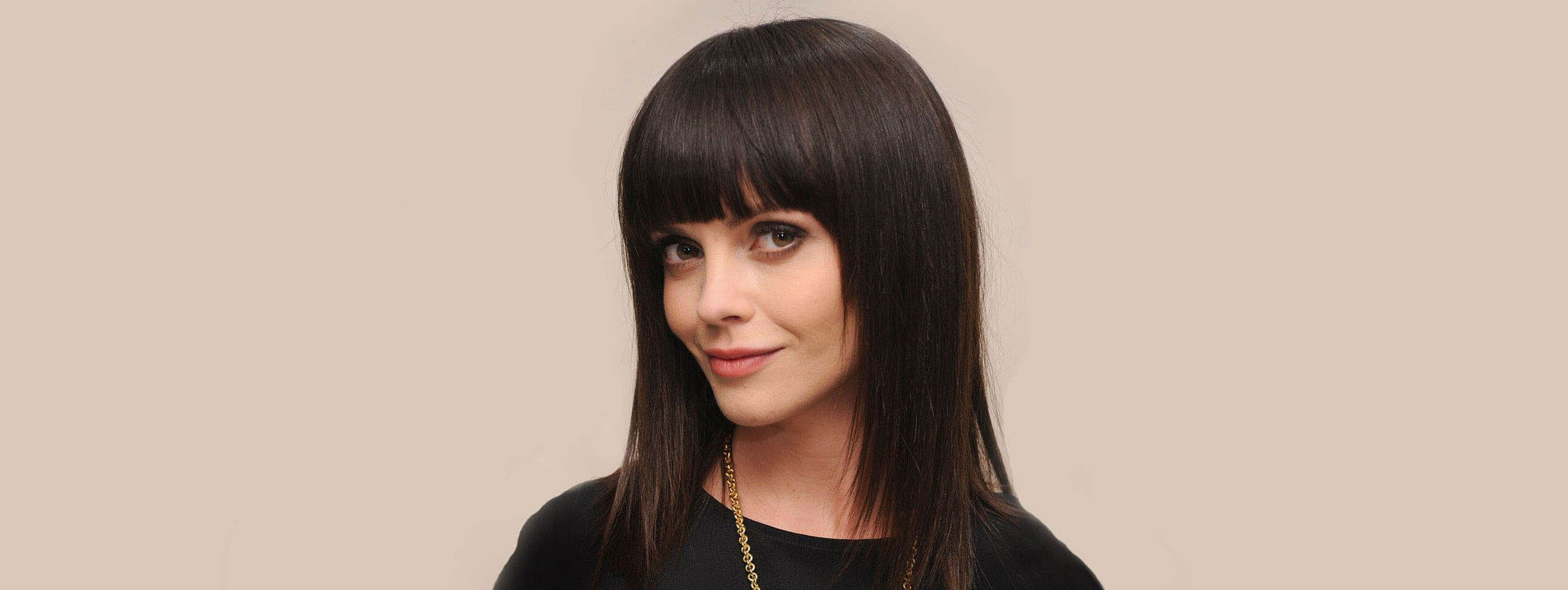 Woman with long, dark, straight, fringed hairstyle
