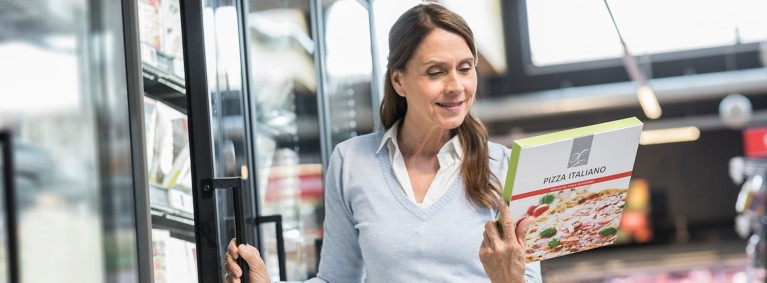 Woman reading the contents of a pizza box in the freezer section of the grocery store