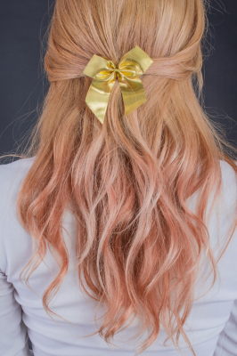 A young woman with pink wavy hair with a yellow bow, pictured from behind