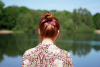 Rear view of a red-haired young woman with a top knot standing by a lake.