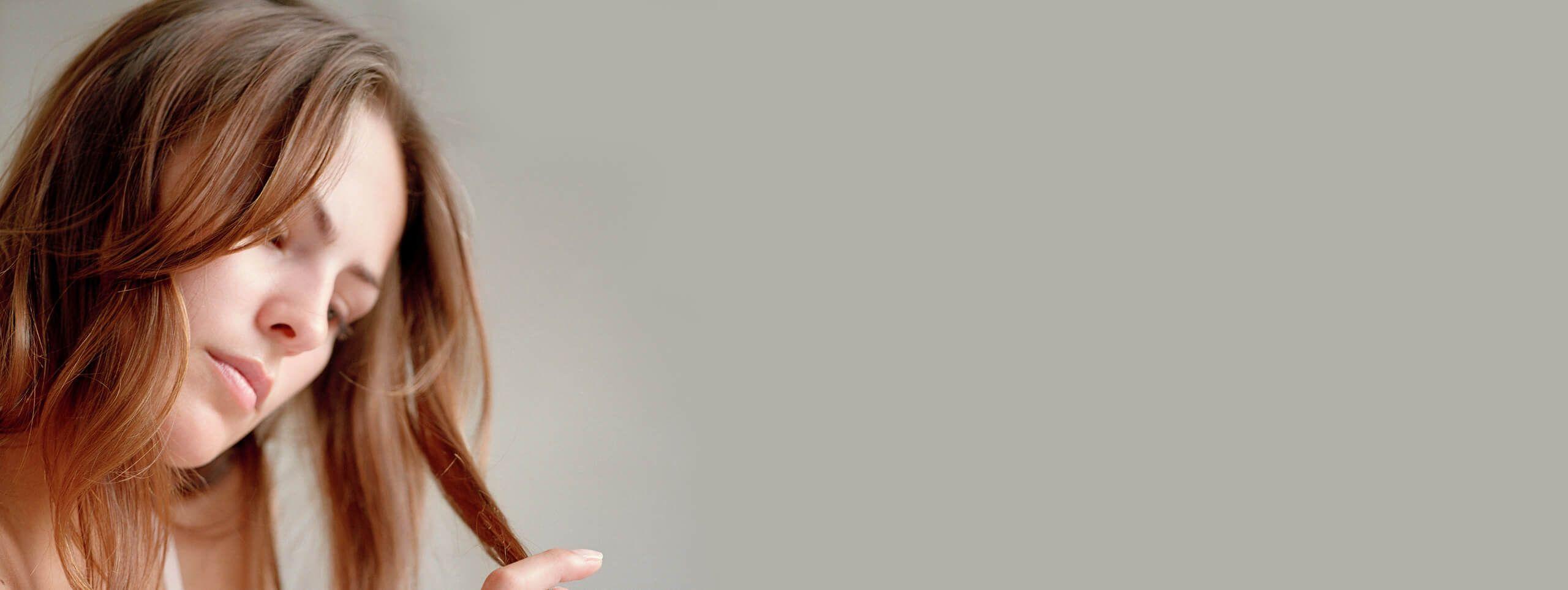 Zmartwiona kobieta trzymająca końce włosów